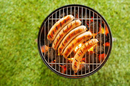 Foto de View from above on a green grass background of a row of pork and beef bratwurst grilling over a barbecue fire on a hot day during the summer vacation - Imagen libre de derechos