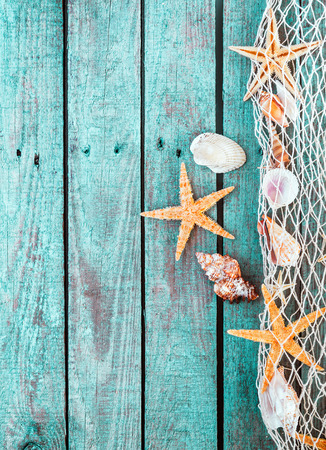 Photo pour Marine border of fishing net with shells and starfish on rustic turquoise blue wooden planks with a weathered woodgrain texture and copyspace - image libre de droit