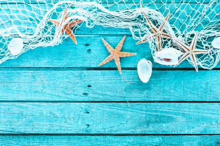 Photo pour Delicate nautical border with fishing net, sea shells and starfish on a background of colourful turquoise blue painted wooden boards with copyspace for your text - image libre de droit