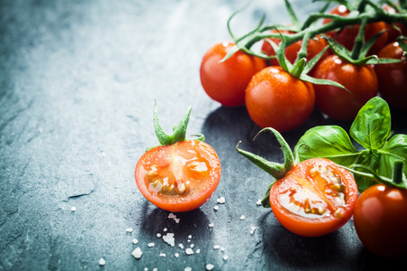 Foto de Fresh grape tomatoes with basil and coarse salt for use as cooking ingredients with a halved tomato in the foreground with copyspace - Imagen libre de derechos