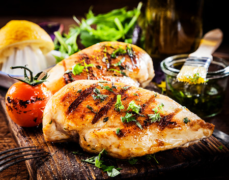 Photo pour Marinated grilled healthy chicken breasts cooked on a summer BBQ and served with fresh herbs and lemon juice on a wooden board, close up view - image libre de droit