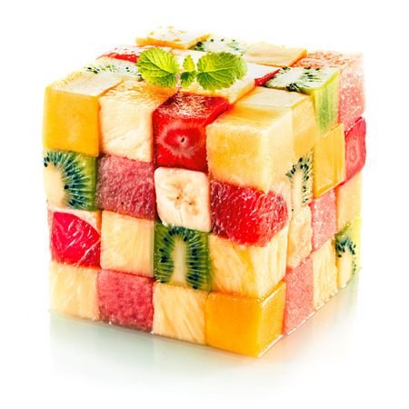 Foto de Fruit cube formed from small squares of assorted tropical fruit in a colorful arrangement including kiwifruit, strawberry, orange, banana and pineapple on a white background - Imagen libre de derechos