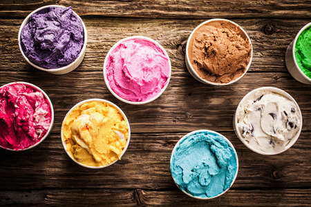 Photo for Selection of gourmet flavours of Italian ice cream in vibrant colors served in individual plastic tubs on an old rustic wooden table in an ice cream parlor, overhead view - Royalty Free Image