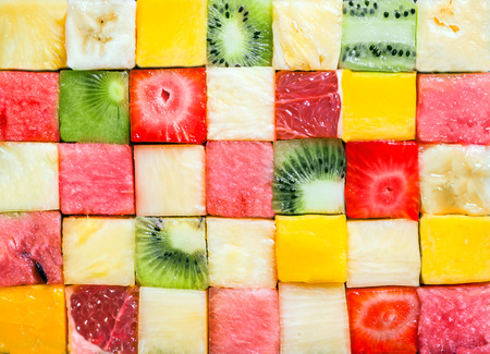 Foto de Seamless background pattern and texture of colourful fresh diced tropical fruit cubes arranged in a geometric pattern with melon, watermelon, banana, pineapple, strawberry, kiwifruit and grapefruit - Imagen libre de derechos