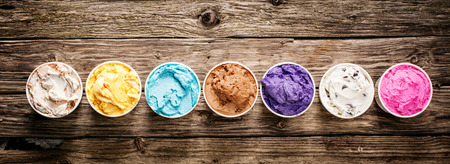 Row of assorted flavors and colors of gourmet Italian ice cream served in plastic takeaway tubs on a rustic wooden table, horizontal banner format with copyspace