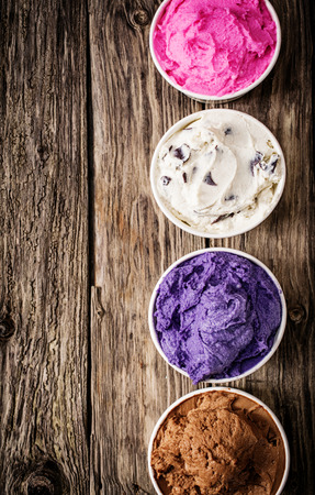 Photo for Colorful selection of Italian ice cream tubs viewed from above filled with delicious frozen dessert for a party or summer treat on an old wooden table with copyspace - Royalty Free Image