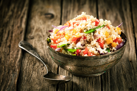 Photo pour Healthy vegetarian quinoa recipe with colourful bell pepper, tomato, onion and fresh herbs in a rustic metal bowl on an old wooden kitchen counter - image libre de droit