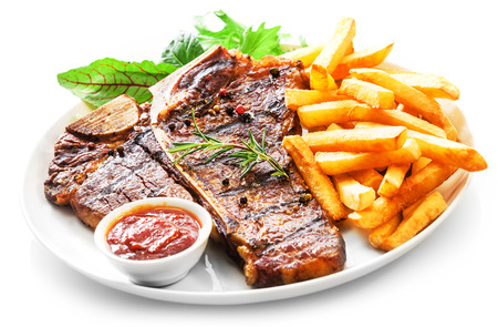 Foto de Tender grilled porterhouse or t-bone steak served with crisp golden French fries and fresh green herb salad accompanied by a BBQ or tomato ketchup sauce - Imagen libre de derechos