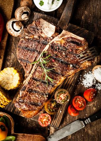 Foto de Grilled t-bone or porterhouse steak seasoned with rosemary in a rustic kitchen on a wooden board with tomatoes, corn, mushrooms and salt, overhead view - Imagen libre de derechos