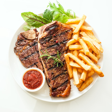 Foto de Grilled t-bone or porterhouse steak seasoned with rosemary and served with golden French fries, fresh leafy herb salad and a tomato dip, high angle view on white - Imagen libre de derechos