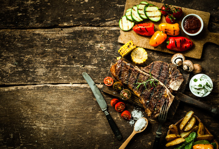 Photo pour Overhead view of colorful roast vegetables, savory sauces and salt served with grilled t-bone steak on a rustic wooden counter in a country steakhouse - image libre de droit