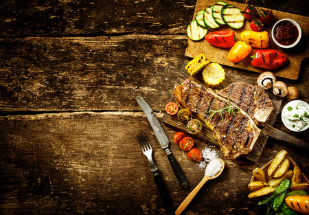 Photo for Preparing t-bone steak and roast vegetables in a country kitchen with bell peppers, mushrooms, tomato, potato, mangetout peas, and corn on a rustic wooden table with copyspace - Royalty Free Image