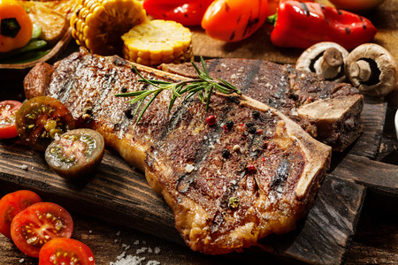 Foto de Close up of a succulent tender grilled porterhouse steak seasoned with pepper and rosemary on a wooden board with fresh halved tomatoes, mushrooms, corncobs and bell peppers - Imagen libre de derechos