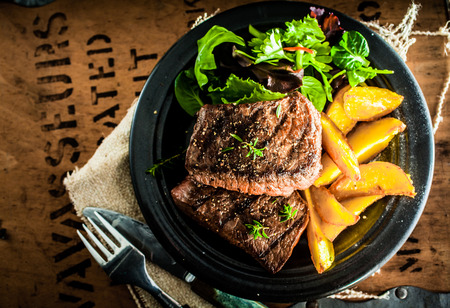 Photo for Overhead view of delicious,grilled beef steak with roasted pumpkin and fresh green herb salad on an old wooden packing case with printed text - Royalty Free Image