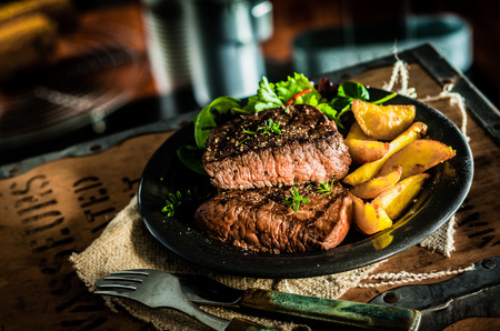 Photo pour Healthy lean grilled medium-rare beef steak and vegetables with roasted pumpkin and a leafy green herb salad in a rustic pub or tavern - image libre de droit