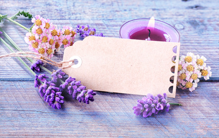 Photo for Spa, relaxation and wellness background with a blank gift tag or label with copyspace amongst fresh lavender and flowers with a burning candles for aromatherapy treatment on rustic blue wooden boards - Royalty Free Image