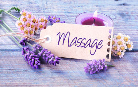 Foto de Spa massage background with fragrant fresh lavender and flowers with a burning aromatherapy candle around a label or gift tag with the script - Massage - on rustic blue boards - Imagen libre de derechos