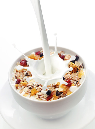 Photo pour Milk splashing into a bowl of fresh muesli with a mix of wheat, oats and bran with dried fruit and nuts over white with copyspace - image libre de droit