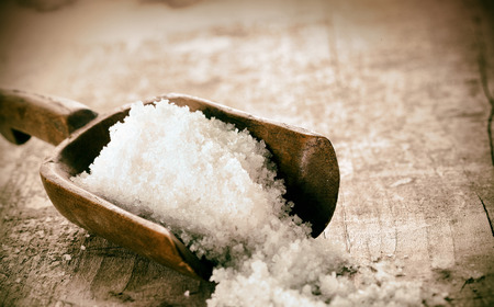 Photo pour Coarse granules of natural rock or sea salt in a rustic old wooden ladle spilling out onto a grunge wooden table - image libre de droit
