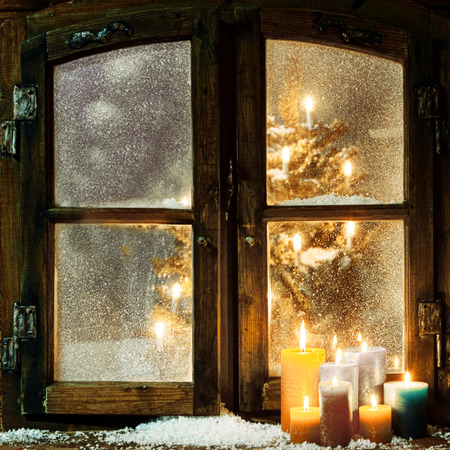 Photo pour Welcoming Christmas window in a log cabin with a group of burning candles on the windowsill and a glowing Christmas tree visible through the frosted panes - image libre de droit