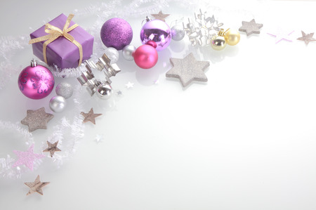 Photo pour Christmas background with a decorative border of elegant silver, pink and purple stars, baubles, cookie cutters and a gift over white with copyspace - image libre de droit