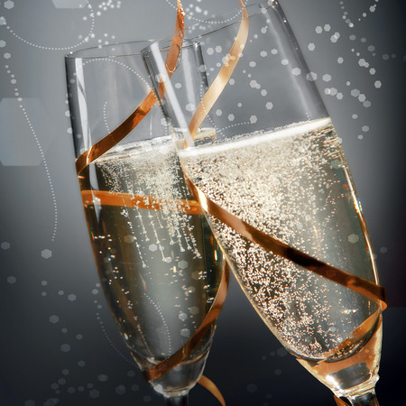 Photo pour Romantic flutes of sparkling golden champagne with effervescent bubbles wrapped in golden ribbon to celebrate a wedding, Valentines, New Year or anniversary, close up detail on grey - image libre de droit