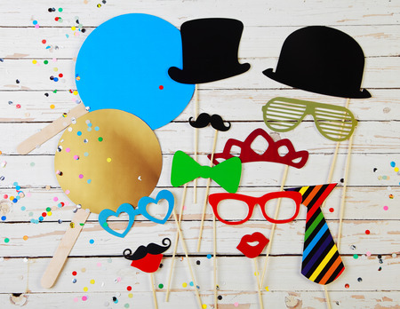 Photo pour Trendy colorful party background of fun photo booth accessories for comic disguise and multicolored confetti on rustic white wooden boards - image libre de droit
