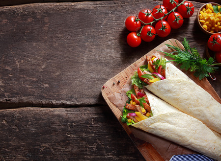 Foto de Preparing tasty Tex-Mex tortilla wraps in a rustic kitchen filled with fresh salad ingredients, corn kernels, herbs and diced meat , overhead view with ingredients and copyspace - Imagen libre de derechos