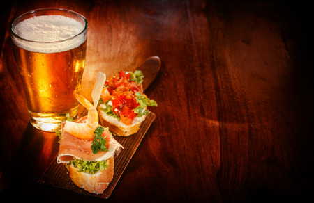 Photo pour Glass of cold beer with delicious tapas topped with shrimp, parma ham and tomato on baguette served on a wooden bar or pub counter for tasty snacks - image libre de droit