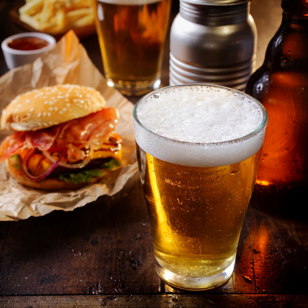 Photo pour Glass of chilled beer served with a cheeseburger and French fries for a relaxing lunch in a pub or bar - image libre de droit