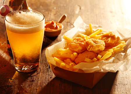 Photo pour Chilled glass of draft beer served with fried battered fish and French fries accompanied by a savory dip in a bar, tavern or pub - image libre de droit