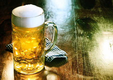Photo pour Glass beer mug with golden ale or draft topped with a frothy head standing on an old wood counter in a bar or pub with copyspace - image libre de droit