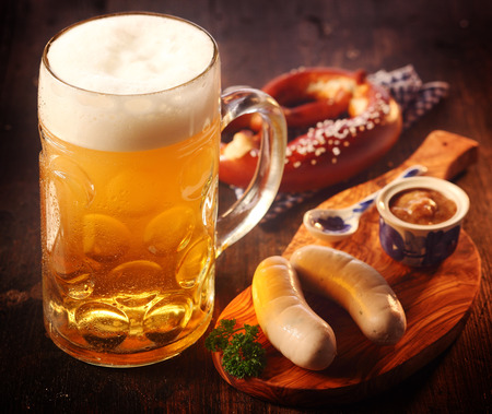 Foto de Glass tankard or mug of cold draft beer with German sausages and pretzels with mustard served on a wooden board for refreshments conceptual of Oktoberfest - Imagen libre de derechos
