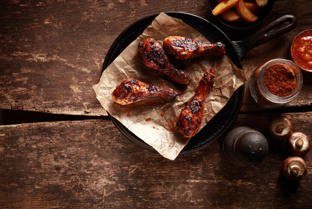 Photo pour High Angle Looking Down at Saucy Barbecued Chicken Drumsticks on Cast Iron Pan Accompanied by Spices and Ingredients - image libre de droit
