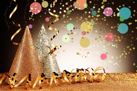 Photo for Close up Glittery Carnival Cone Hats and Gold Streamers with Confetti Effect on Glittery Table in Front Gradient Brown Background - Royalty Free Image