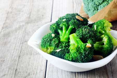 Photo pour Close up Flavored Steamed Fresh Broccoli on White Plate, Served on Top of Wooden Table. - image libre de droit
