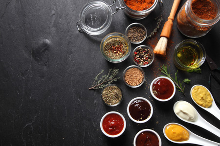Foto per Various Spicy Ingredients for Recipe on Black slate Table with Copy Space on Left Side. - Immagine Royalty Free