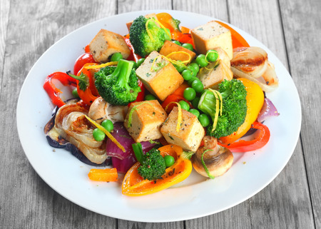 Photo for Close up Gourmet Healthy Main Dish on White Plate with Tofu, Broccoli, Mushrooms, Beans and Spices. Served on Wooden Table - Royalty Free Image
