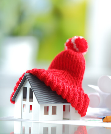 Foto de Energy saving Shot of Conceptual Red Knitted Hat on Top of Miniature House for isolation and insulation concepts - Imagen libre de derechos