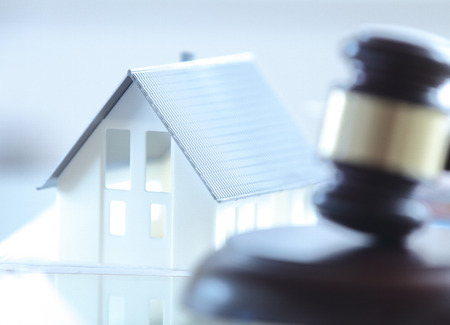 Foto de Close up Conceptual White Miniature House on Top of the Table Beside Court Gavel. - Imagen libre de derechos