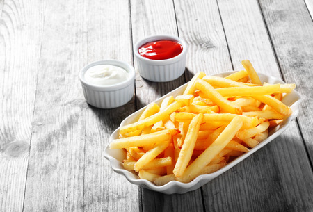 Photo pour Close up Crispy Potato Fries on White Plate with Two Dipping Sauce, Served on Rustic Wooden Table - image libre de droit