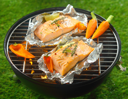 Foto de Grilled salmon steaks with baby vegetables cooking on tin foil over a barbecue outdoors in summer with baby carrots and sweet pepper - Imagen libre de derechos