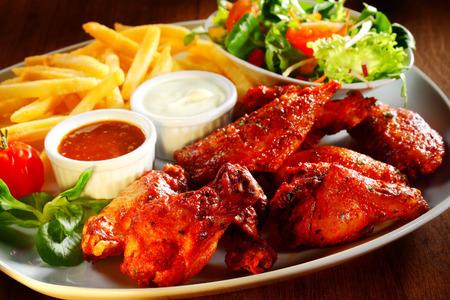 Foto de Close up Gourmet Appetizing Fried Chicken with Two Sauces, Potato Fries and Veggies on a Plate. - Imagen libre de derechos