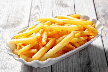 Foto per Close up Tasty Fried Potato French Fries on White Plate on Top of Wooden Table. - Immagine Royalty Free