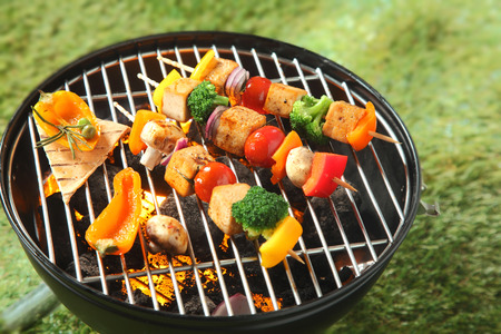 Photo pour Tofu kebabs with colorful fresh vegetables including onion, sweet pepper, tofu,mushroom, broccoli and tomato threaded on skewers grilling over the fire on a BBQ - image libre de droit