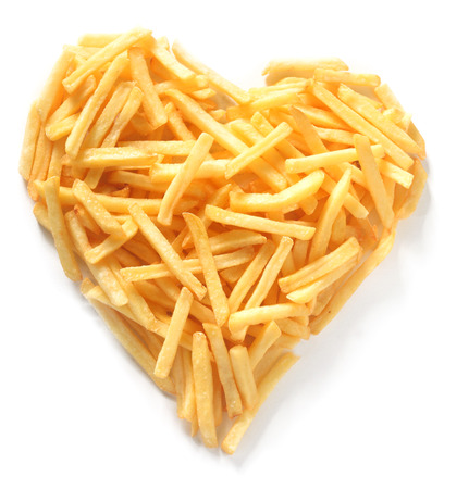 Foto per Overhead Still Life of Thin Straight Cut French Fries in Shape of Assymmetrical Heart on White Background - Immagine Royalty Free