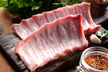 Close up Raw Pork Rib Meat Ingredient on Top of Rustic Wooden Cutting Board