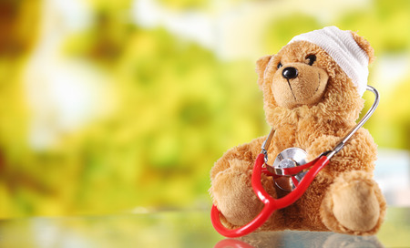 Foto de Close up Bandaged Plush Teddy Bear with Stethoscope Device on Top of a Glass Table, Emphasizing Copy Space. - Imagen libre de derechos