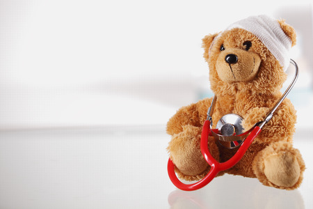 Foto de Close up Bandaged Teddy Bear on the Table Top with Stethoscope Device on White Background, Emphasizing Copy Space on the Left Side. - Imagen libre de derechos