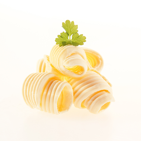Foto de Rolled coils of fresh creamy butter garnished with parsley for a gourmet food presentation isolated on white - Imagen libre de derechos